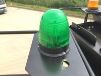wheeled excavator hire with green seat belt beacon
